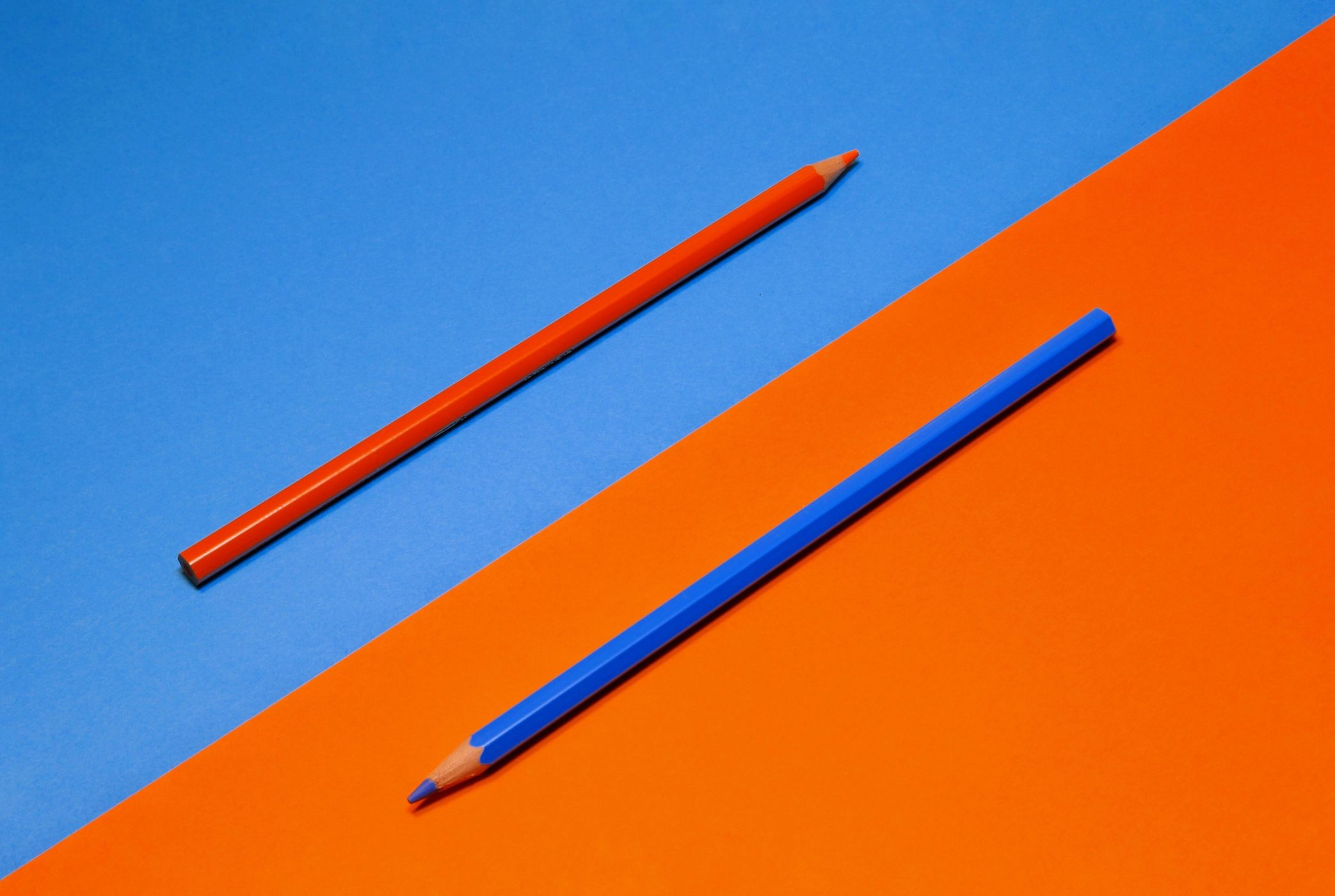 a blue triangle with an orange pencil resting in the center; an orange triangle with a blue pencil resting in the center. both pencils are at a 45-degree angle.