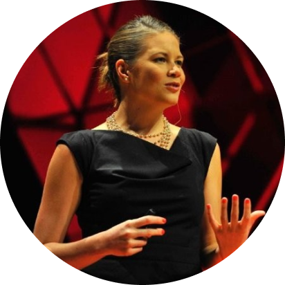 medium shot of a light-skinned woman with brown hair, pulled back into a bun, wearing a black dress and colorful beads, standing and gesturing with both hands as though she's in the middle of giving an impassioned speech. background is a display of red and black lights.