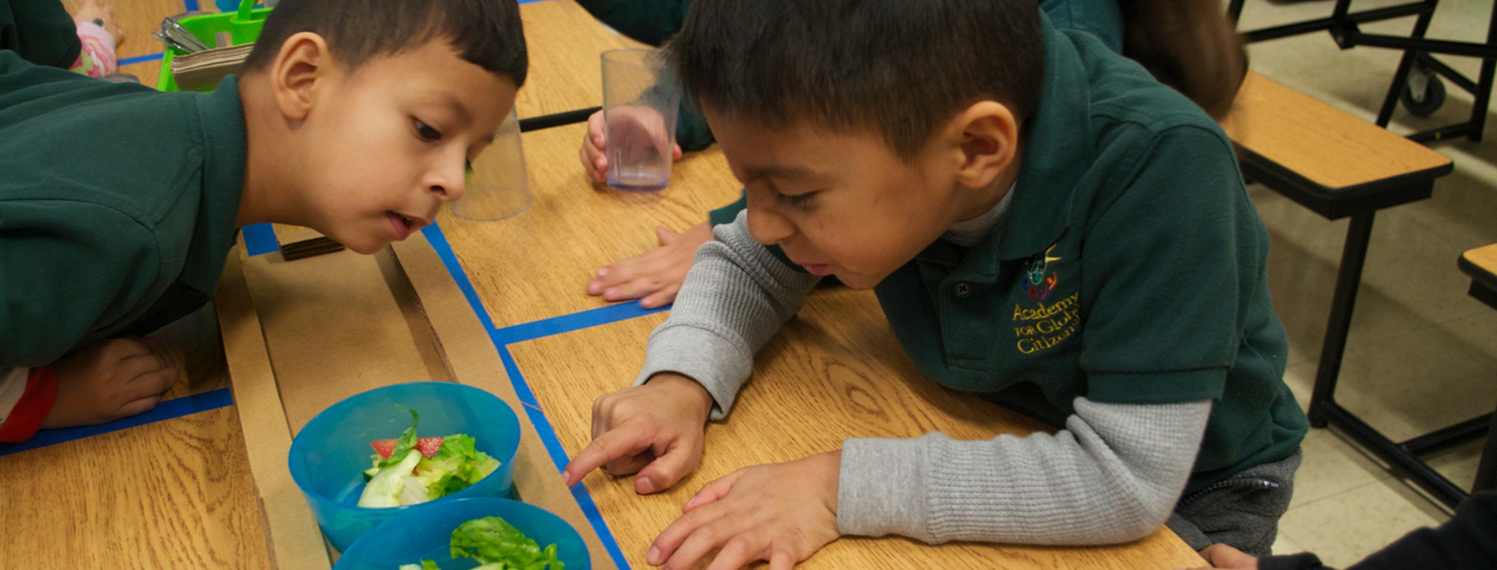 two medium-skinned boys wearing dark green school-uniform polo shirts sit on benches at a long, wood-paneled school cafeteria table. a brown cardboard tray sits in the middle of the table with multiple blue plastic bowls holding salad. the boy on the right points at a bowl of salad with a disgusted look on his face. the boy on the left leans all the way over the tabletop to see what the boy on the right is pointing at.