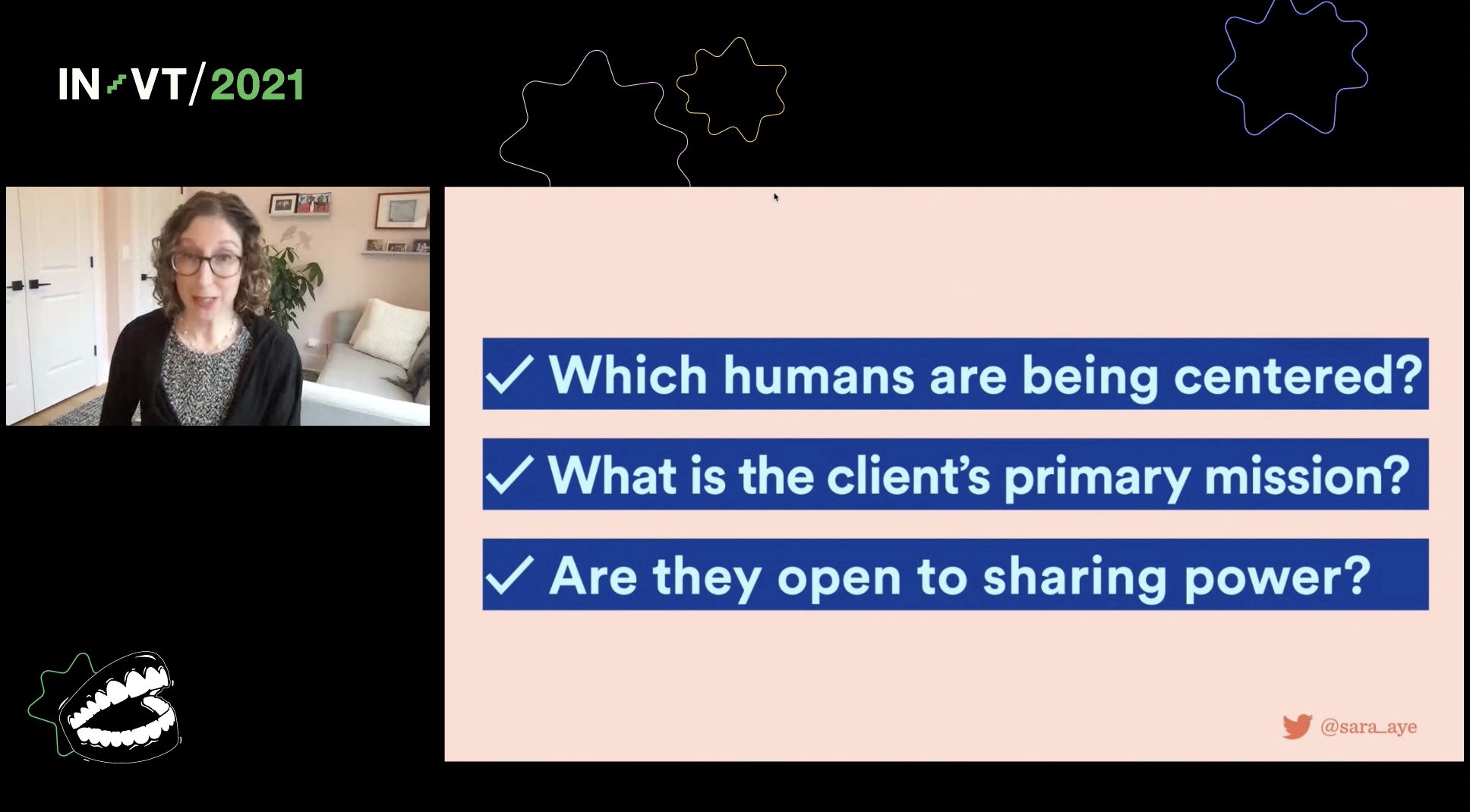 """a black backdrop with a small rectangle in the top left of a light-skinned woman with wavy brown hair and round gray glasses looking mid-sentence, and a large slide share with three questions, blue text on a light pink background: """"Which humans are being centered? What is the client's primary mission? Are they open to sharing power?"""""""