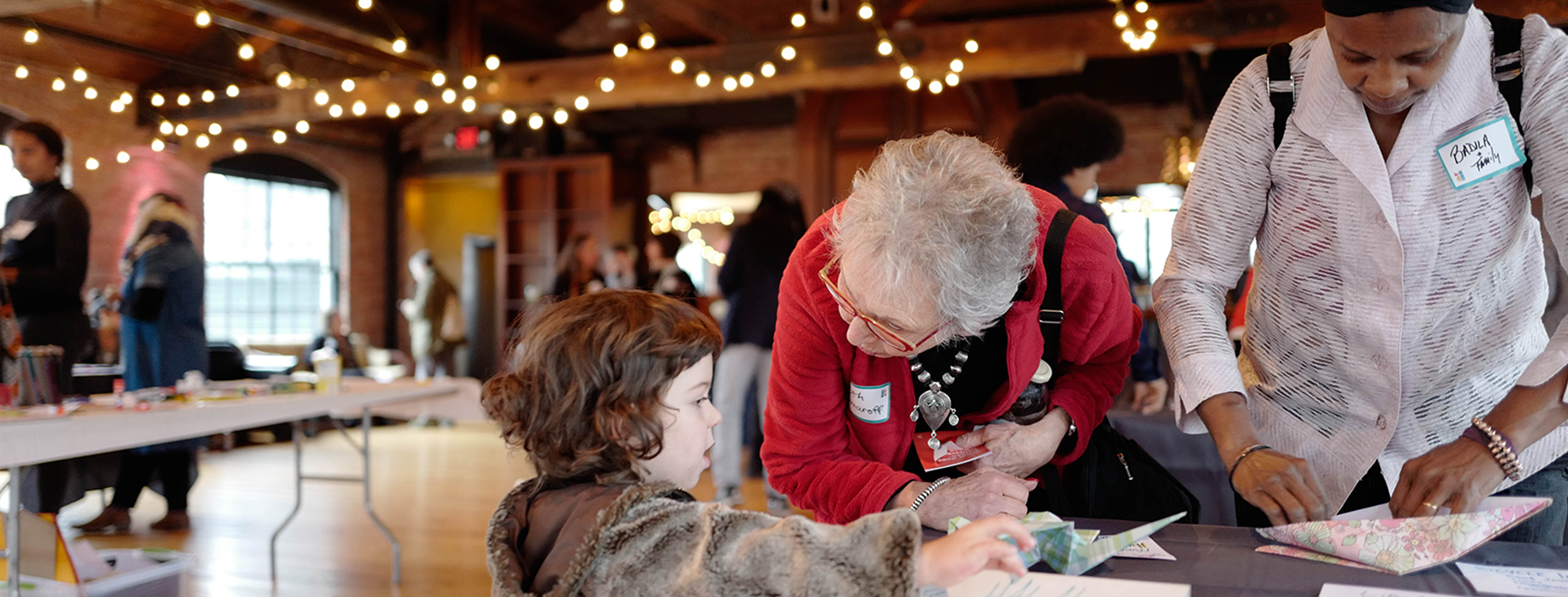 a woman with gray hair and light skin in a red sweater leans forward over a table, her head turned towards a young light-skinned girl in a furry brown coat. next to them, a medium-skinned woman in a white shirt and black head wrap folds a piece of paper. they are in a room with tall ceilings, exposed wooden rafters and string lights.